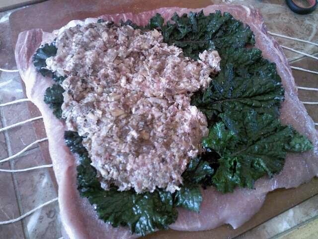Butterflied pork loin covered with kale and stuffing and ready to roll up.